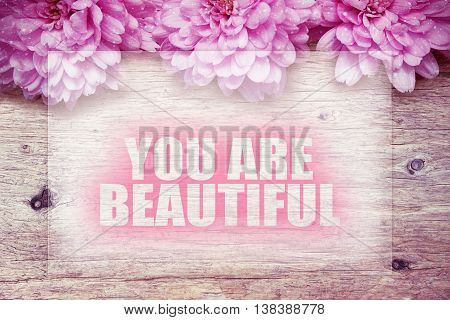 pink flowers on wooden with word you are beautiful