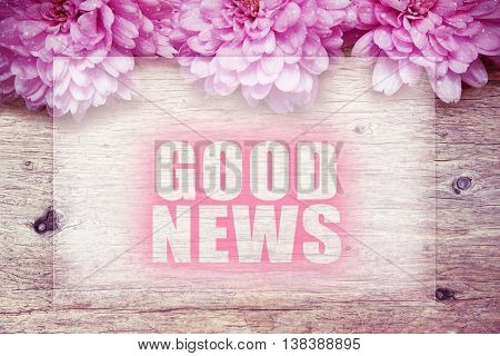 pink flowers on wooden with word Good News