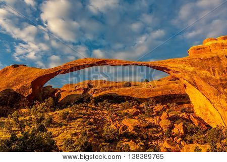 A big rock arch illuminated in the morning in Arches National Park