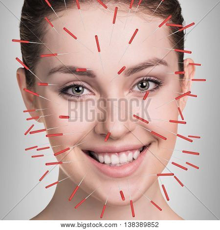 Closeup of performing acupuncture therapy on face over gray background
