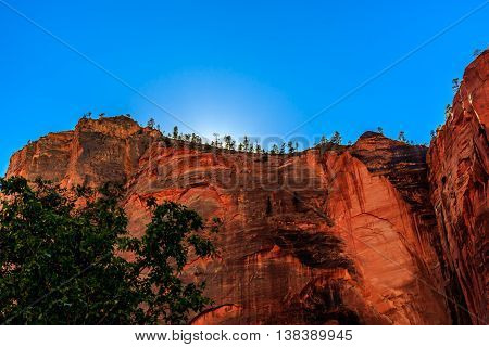 The sun behind Angel's Landing in Zion National Park
