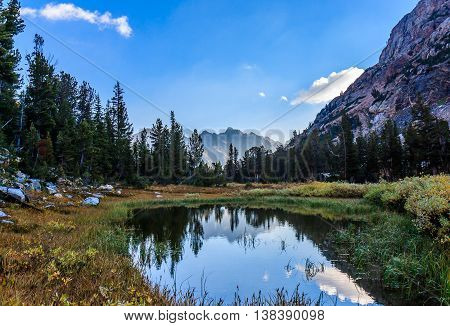 A glassy lake in the forest and mountains of Grand Teton National Park