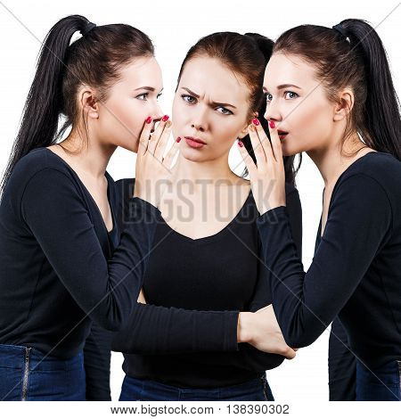 Brunette girls telling gossip to another angry girl isolated on white
