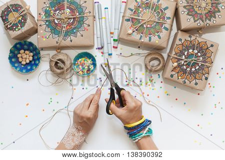 Gifts wrapped in kraft paper. On boxes painted mandala pattern.