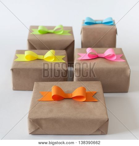 Gifts wrapped in kraft paper. Coloured bright paper bows.