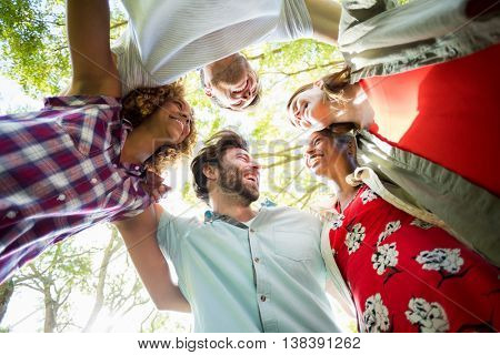 Group of friends forming huddles in park
