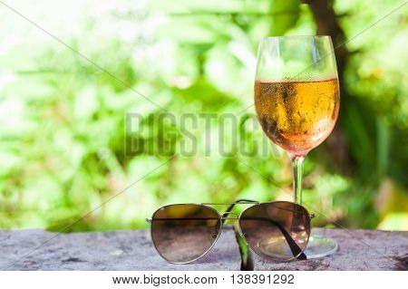 glass of chilled rose wine on table over tropical background