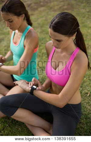 Beautiful women adjusting a time on wristwatch in park