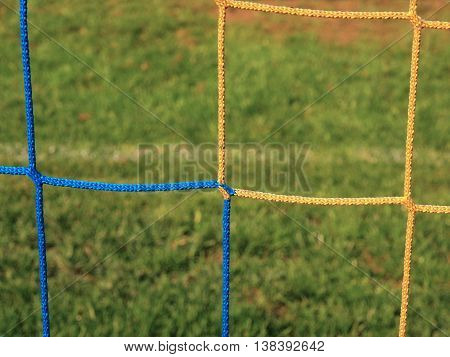 Detail of yellow blue crossed soccer nets, soccer football in goal net with grass on outdoor playground in the background.