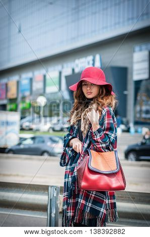 Outdoor fashion portrait of glamour sensual young stylish lady wearing trendy fall outfit hat and leather bag.