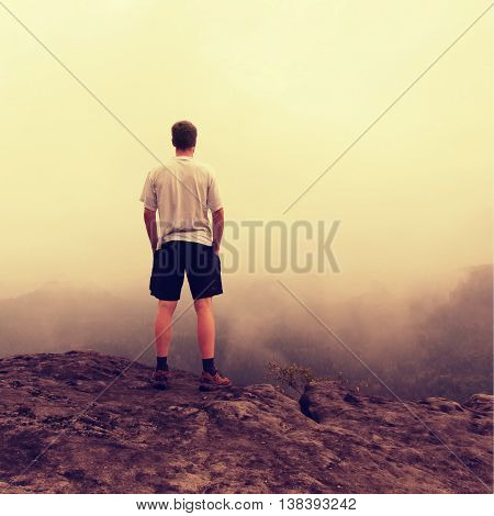Man in white shirt and black pants stand on rock in national park and enjoy beautiful moment of miracle of nature