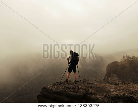 Silhouette of tourist. Sunny spring daybreak in rocky mountains. Hiker with sporty backpack stand on rocky view point above misty valley.