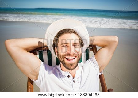 Happy young man relaxing on armchair at beach