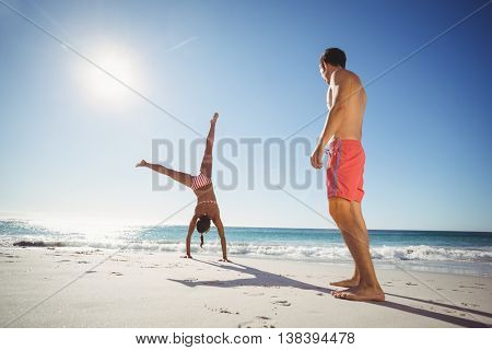 Man watching woman while performing somersault on beach