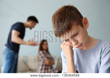 Family problems concept. Sad boy and abusing parents