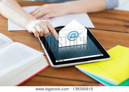 communication, education, technology and internet concept - close up of student woman with e-mail icon on tablet pc computer and notebook at home
