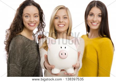 Studio portrait of three teenage girls holding a piggybank