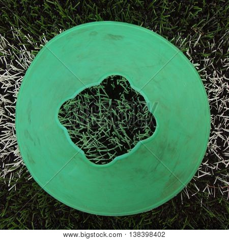 Bright green blue plastic cone on painted white line. Plastic football green turf playground with grind black rubber in core.