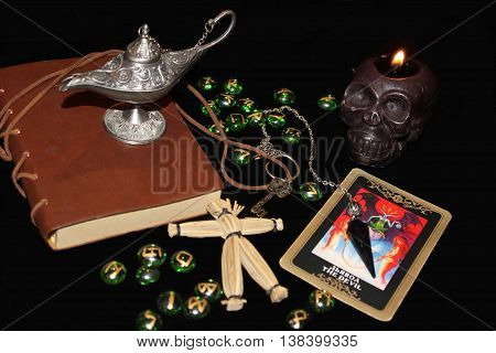Black magic ritual objects, symbols and elements on the black background.Black burning skull candle, voodoo doll, old magic book, pendulum with chain, devil tarot card, magic aladdin lamp