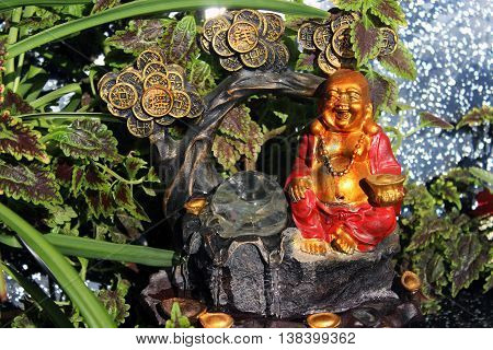 Feng Shui  desktop fountain with water, plants, gold coins, magic crystal ball and chinese traditional smiling happy Buddha. Symbol of good luck, wealth, prosperity, love.