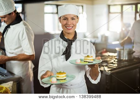 Portrait of chef presenting dessert plates in commercial kitchen