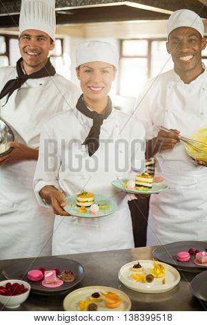 Portrait of chefs preparing a dessert in commercial kitchen