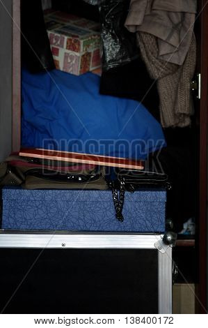 Vertical cropped shot of an open waredrobe with clothes and boxes stacked