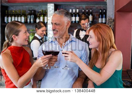 Friends toasting with a glass of red wine at bar counter in a bar
