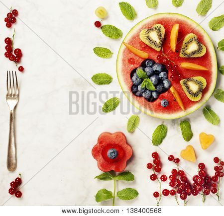 Summer fruit concept. Watermelon, fruits, berries and mint leaves on white marble background. Healthy food concept. Flat lay