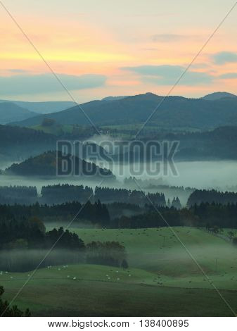 View into autumn deep misty valley in Bohemian national park, Europe. Trees and hills increased from foggy background. Colorful sky above horizon.
