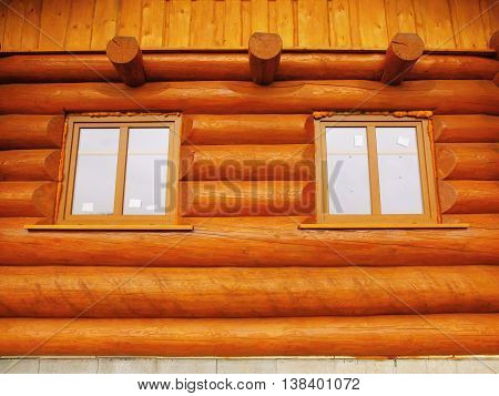 Detail of window built in wooden beams cabin wall. Painted wood with fungicide light red paint.