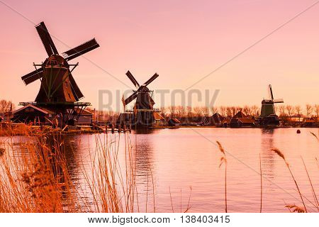 Sunset panoramic view of windmills and lake in Zaanse Schans, traditional village in Holland, copy space