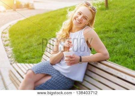 Portrait of happy blonde woman sitting on bench with drink on summer day. Image with tilt-shift effect and lens flare effect