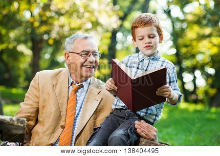 Grandfather and grandson are reading book and learning about nature
