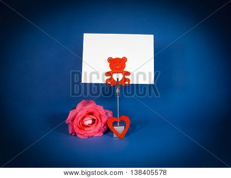 Note holder with roses and empty card on blue