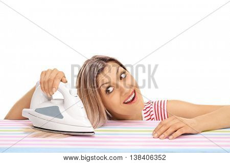 Young woman ironing her hair with an iron isolated on white background