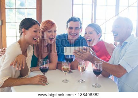 Group of friends looking at the mobile phone in restaurant