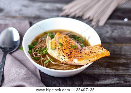 Bowl of soba noodle salmon asian soup Roasted fried salmon with spicy ginger stock on wood background