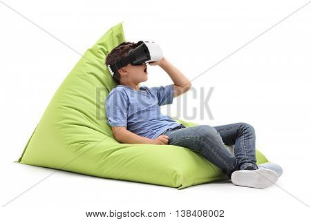 Joyful kid looking in a VR goggles seated on a comfortable green beanbag isolated on white background