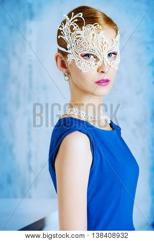 Beautiful young woman in elegant evening dress and carnival mask standing by a vintage wallpaper. Fashion shot. Retro hairstyle.