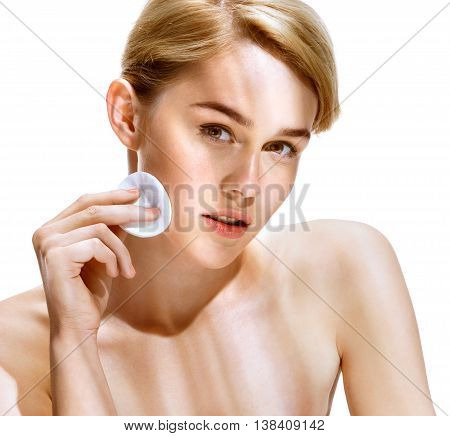 Young woman cares for face skin relaxation. Close up of an attractive girl of European appearance on white background. Beauty & Spa Concept.