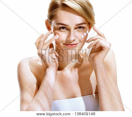 Portrait of young woman applying moisturizer cream on her pretty face. Youth and Skin Care Concept.