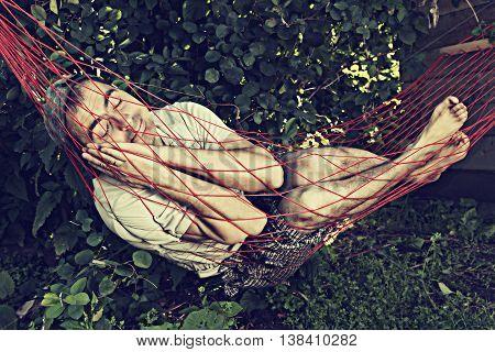 Funny man barefoot sleeping in a hammock.