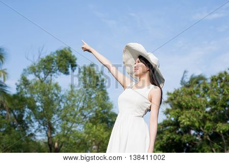 young woman wear dress and pointing something ; nature green background
