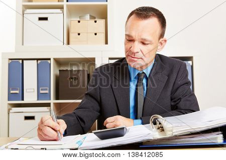 Accountant during tax audit in office with pen and calculator
