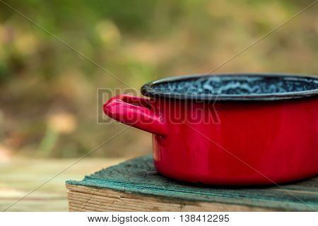 Vintage red enamel pan for cooking on wooden board on natural background