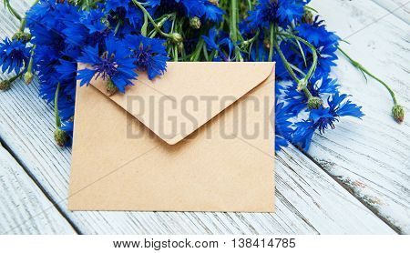 Blue fresh cornflowers with envelope on a old wooden table