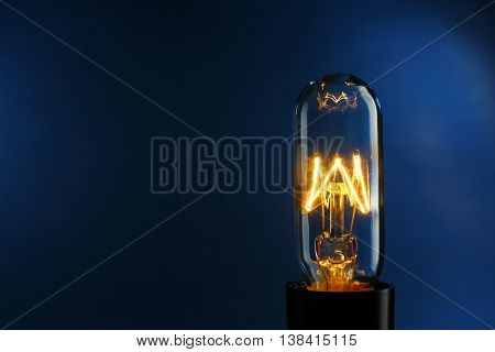 Illuminated light bulb on dark blue background