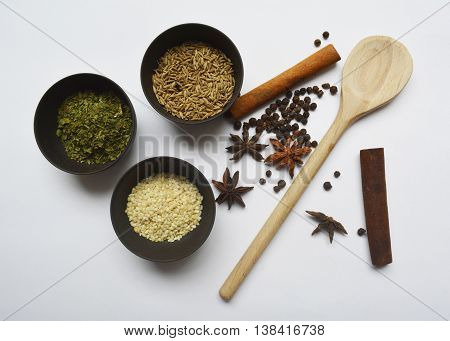 spices and seasonings at the table - sesame seeds, cinnamon, dried herbs, star anise, cumin seeds