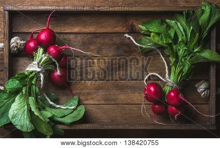 Fresh radish banches on wooden tray background. Top view, copy space, horizontal composition
